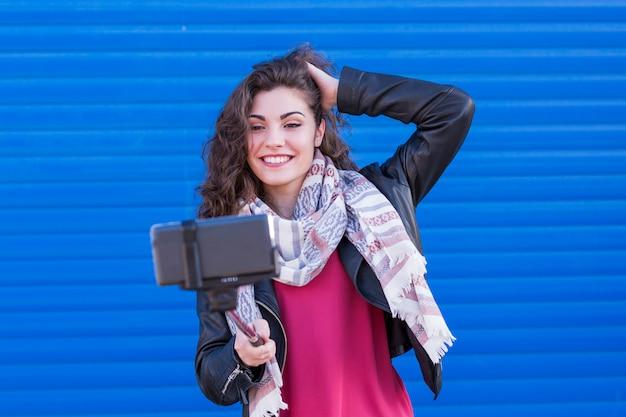 Heureuse belle femme prenant un selfie avec un téléphone intelligent sur fond bleu.