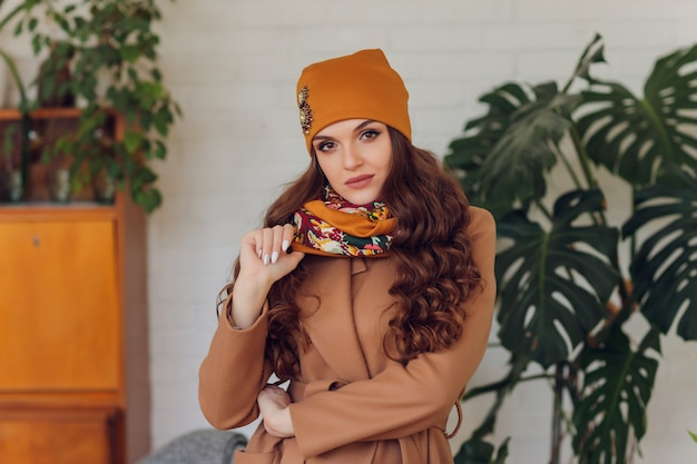 Heureuse belle femme à la recherche d'excitation sur le côté. fille portant un chapeau chaud tricoté et des mitaines.