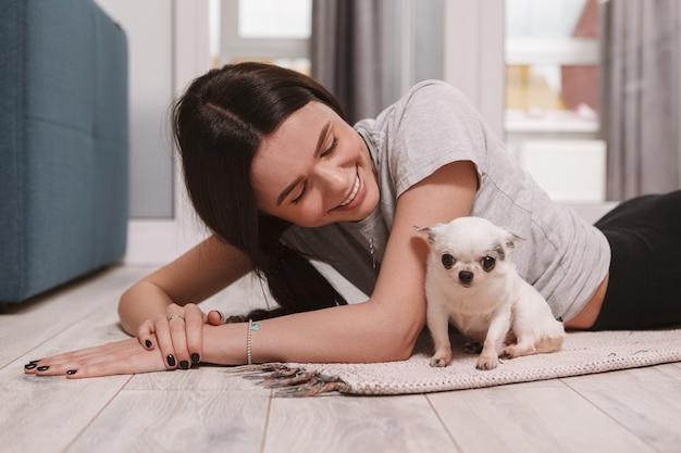 Heureuse belle femme en riant, en regardant son adorable petit chien, allongé sur le sol à la maison