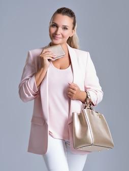Heureuse belle femme avec sac à main et portefeuille dans le shopping