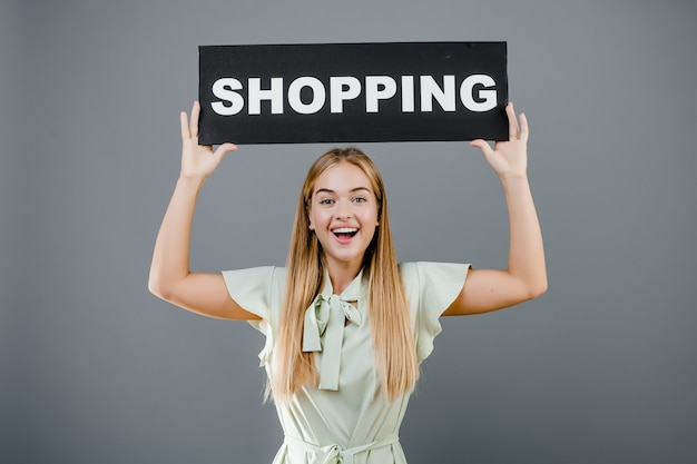 Heureuse belle femme souriante avec shopping signe isolé sur gris