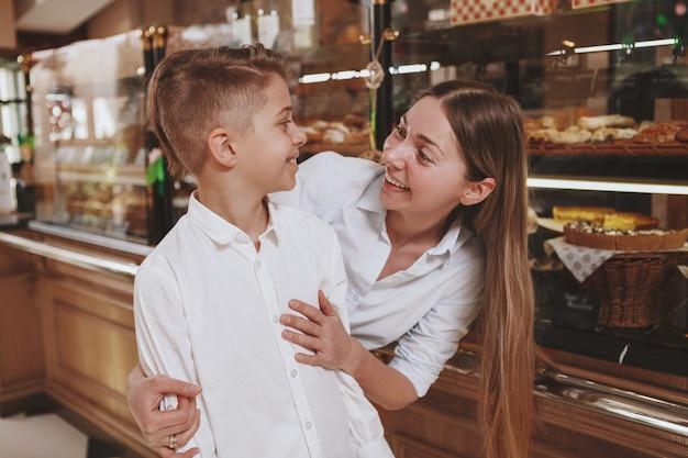Heureuse belle femme souriante à son charmant fils tout en faisant du shopping ensemble pour la pâtisserie au magasin de pain