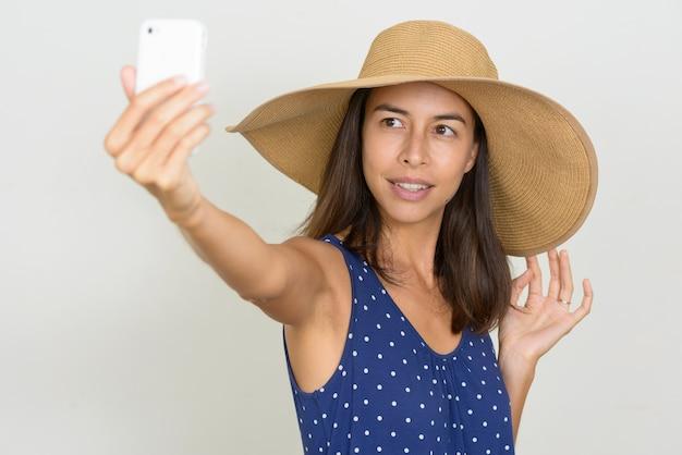 Heureuse belle femme touriste multiethnique prenant selfie