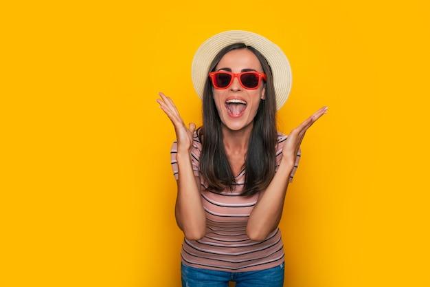Heureuse belle femme touristique excitée en chapeau et lunettes de soleil pose sur fond jaune et s'amuse