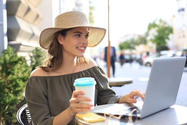 Heureuse belle femme travaillant sur ordinateur portable dans un café de la rue, tenant une tasse en papier.