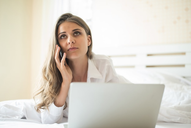 Heureuse belle femme travaillant sur un ordinateur portable sur le lit de la maison