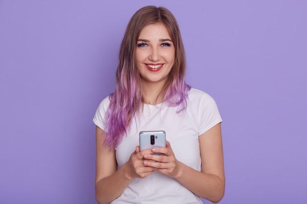 Heureuse belle femme vêtue de blanc occasionnel t shier tenant un téléphone intelligent dans les mains, navigation sur internet ou réseau social, isolé sur un mur violet.