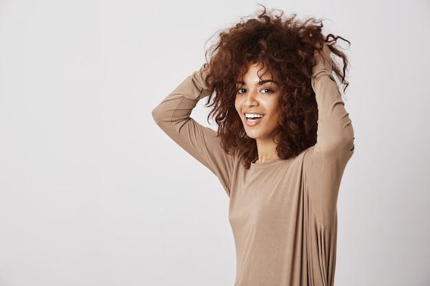 Heureuse belle fille africaine souriante touchant ses cheveux. mur blanc.
