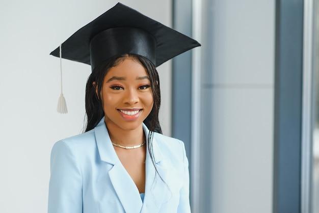 Heureuse belle fille afro-américaine noire avec des diplômés de chapeau