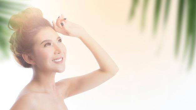 Heureuse belle fille asiatique avec la peau fraîche avec fond de lumière du soleil.