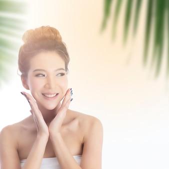 Heureuse belle fille asiatique avec la peau fraîche avec la lumière du soleil