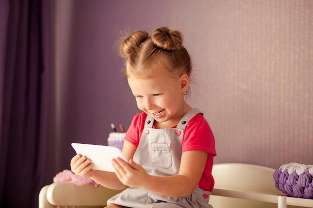Heureuse belle fille assise sur la commode en regardant le smartphone