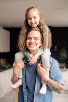 Heureuse belle fille aux cheveux longs assis sur le cou du père et l'embrassant