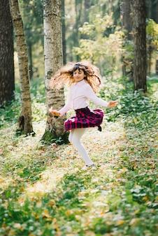 Heureuse belle fille brune tourne et s'amuse dans le parc
