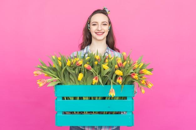 Heureuse belle fille caucasienne brune avec une grande boîte de tulipes sur fond rose.