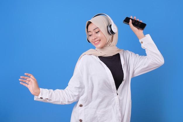 Heureuse belle fille dansant et écoutant de la musique dans des écouteurs sans fil, tenant un smartphone