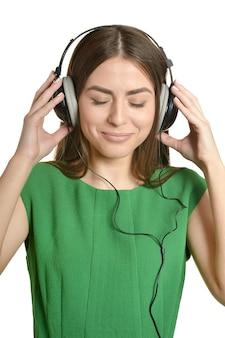 Heureuse belle fille écoutant de la musique dans les écouteurs