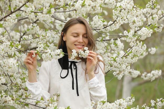 Heureuse belle fille a enlevé son masque médical pour respirer l'odeur des fleurs. une fille dans un masque se tient en fleurs. la fin de la quarantaine