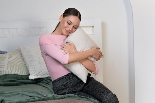 Heureuse belle fille épuisée fatiguée jeune jolie femme détendue est assise sur un lit confortable et