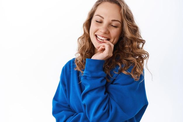 Heureuse belle fille se réjouissant, touchant les lèvres et souriant les yeux fermés, exprime la tendresse et la beauté, debout sur un mur blanc en pull bleu