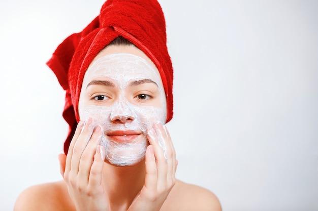 Heureuse belle fille avec une serviette rouge sur la tête applique un gommage sur le visage d'un grand portrait sur fond blanc