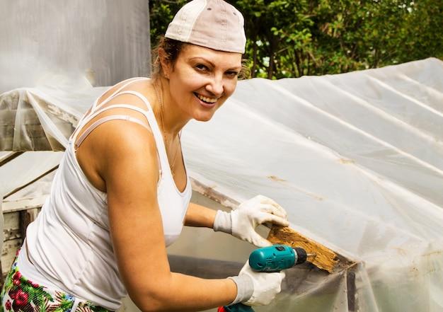 Heureuse belle fille avec un tournevis travaillant dans son jardin, réparant une serre
