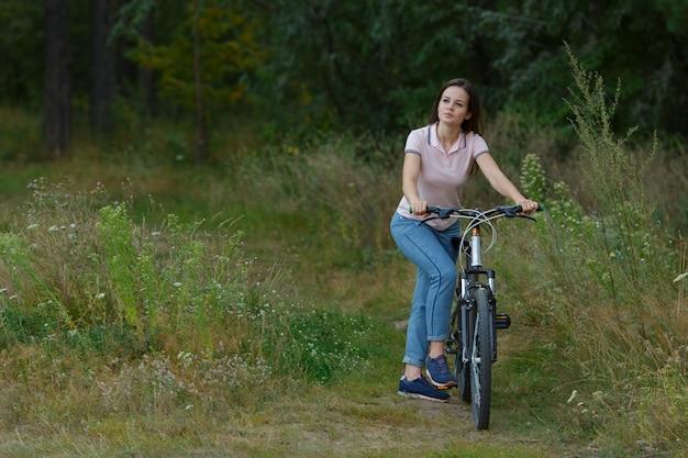 Heureuse belle fille à vélo dans la forêt