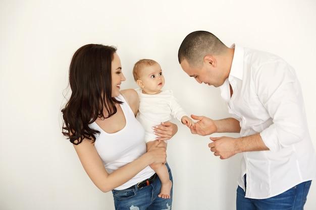 Heureuse belle jeune famille avec bébé souriant embrassant posant sur mur blanc.
