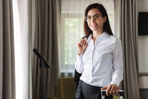 Heureuse belle jeune femme d'affaires dans des vêtements de cérémonie à l'intérieur à la maison avec une valise.
