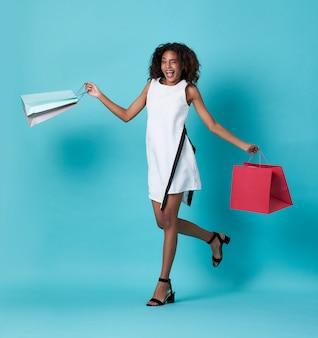 Heureuse belle jeune femme africaine en robe blanche et tenant des sacs shopping sur bleu