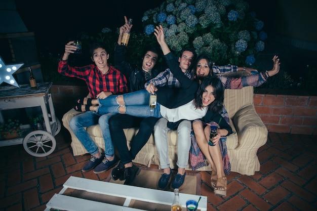Heureuse belle jeune femme allongée sur son groupe d'amis assis dans un canapé et tenant des boissons lors d'une fête en plein air. concept d'amitié et de célébrations.