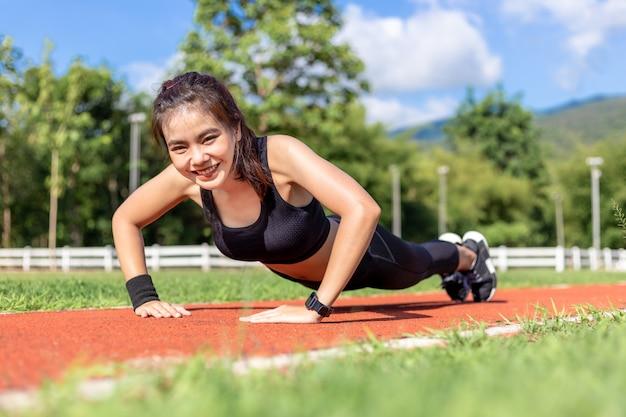 Heureuse belle jeune femme asiatique faisant des exercices de push up le matin sur une piste de course par une journée ensoleillée