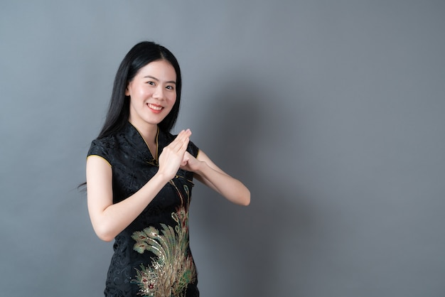 Heureuse belle jeune femme asiatique porter une robe traditionnelle chinoise noire
