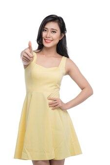 Heureuse belle jeune femme asiatique souriante montrant le geste du pouce en l'air