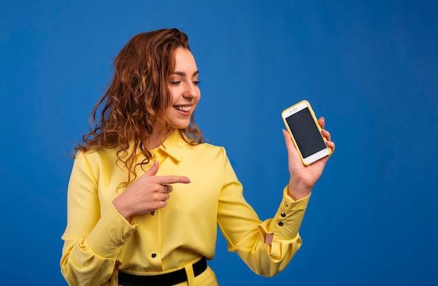 Heureuse belle jeune femme aux longs cheveux bouclés tenant un téléphone mobile à écran blanc