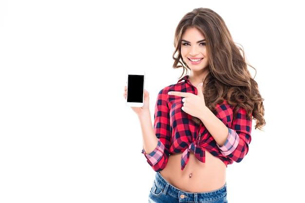 Heureuse belle jeune femme aux longs cheveux bouclés tenant un téléphone portable à écran blanc et pointant dessus sur un mur blanc