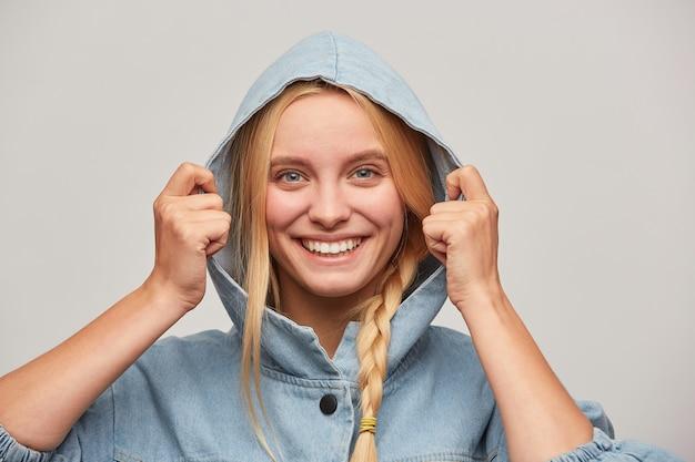 Heureuse belle jeune femme blonde avec tresse, les mains gardent le capuchon, se sent heureux, sourit largement
