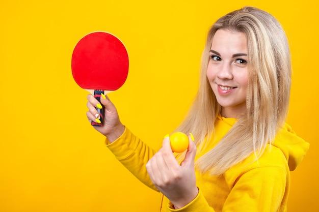 Heureuse belle jeune femme blonde en vêtements de sport jaunes décontractés jouer au ping-pong, tenant une balle et une raquette.