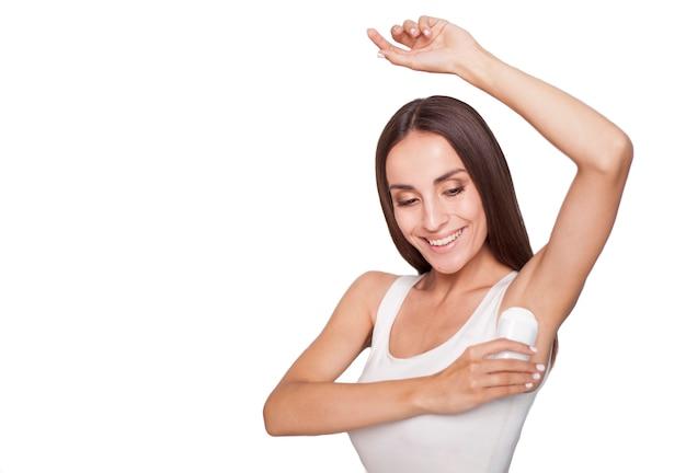 Heureuse belle jeune femme brune utilise un déodorant isolé