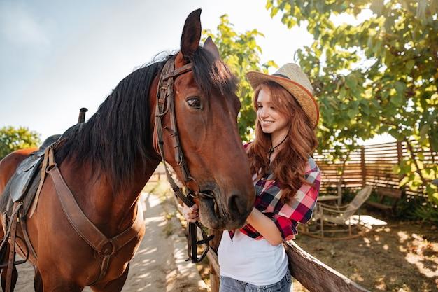 Heureuse belle jeune femme cowgirl au chapeau souriant et en prenant soin de son cheval