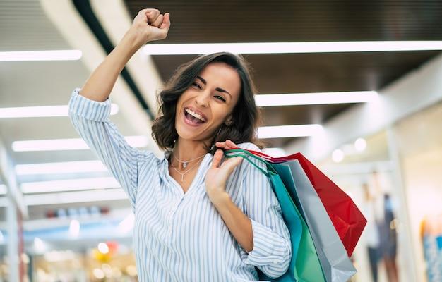 Heureuse belle jeune femme élégante avec des sacs à provisions marchant dans le centre commercial
