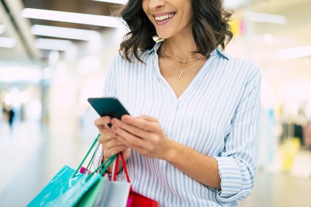 Heureuse belle jeune femme élégante avec des sacs à provisions utilise un téléphone intelligent tout en marchant dans le centre commercial