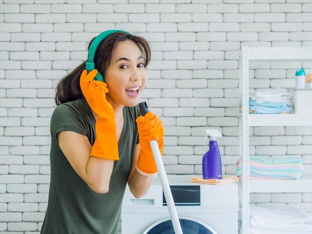 Heureuse belle jeune femme, femme au foyer portant des gants en caoutchouc orange, écouter de la musique avec un casque vert chantant amusant avec une vadrouille comme un microphone sur un mur de briques blanches à la maison.