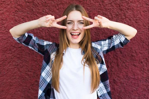 Heureuse belle jeune femme avec le geste de la paix sur fond de mur rouge