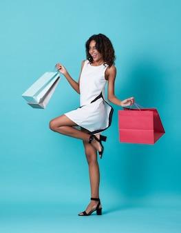 Heureuse belle jeune femme noire en robe blanche et main tenant le sac