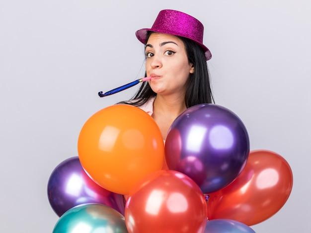 Heureuse belle jeune femme portant un chapeau de fête debout derrière des ballons et soufflant un sifflet de fête isolé sur un mur blanc