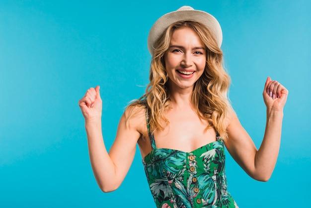 Heureuse belle jeune femme en robe à fleurs et chapeau montrant les poings