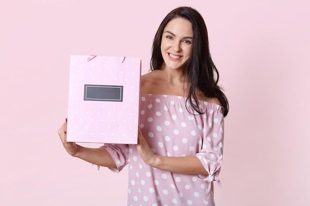 Heureuse belle jeune femme en robe à pois, tenant des sacs à provisions dans ses mains et souriant joyeusement. photo de studio de femme heureuse isolée sur le mur du studio rose concept actuel et anniversaire.