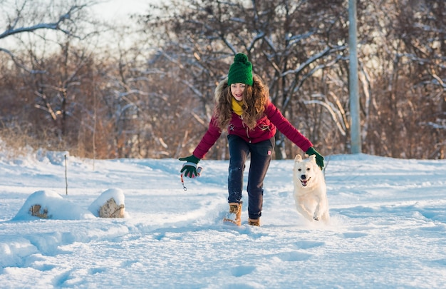 Heureuse belle jeune femme soufflant des flocons de neige de ses mains à son chien golden retriever dans une journée d'hiver