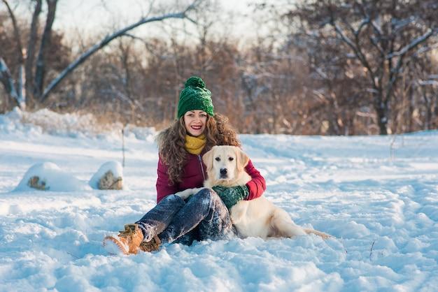 Heureuse belle jeune femme soufflant des flocons de neige de ses mains à son chien golden retriever dans une journée d'hiver.